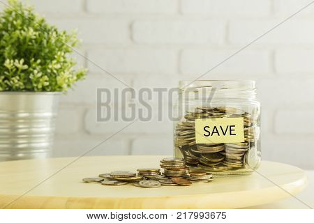 Coins In Saving Glass Jar And On Wooden Table With Yellow Save Tag And White Bricks Background. Save