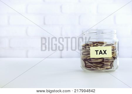 Yellow TAX label on saving glass jar with world coins bricks background vintage retro style. Tax strategies to save business money accounting and financial planning.