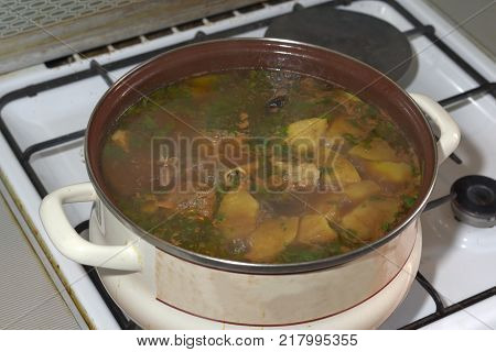 delicious lamb soup boiling on the kitchen stove in the white pan. The famous Azerbaijan dish