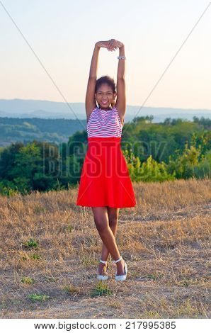 young brasilian tourist with delicious white and red dress with red skirt admires the Tuscan landscape during sunset