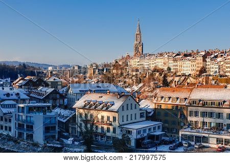 Panorama of snow-covered roofs of Bern's old town and Steeple of Berne Cathedral. Ancient cities of Europe in winter.