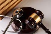 Law mallet or Judge gavel and medical stethoscope near law textbook in library archive study room, close-up. Forensic medicine investigation or malpractice justice concept poster