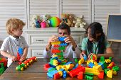 Young family spends time in playroom. Mom dad and boy with toys on room background build out of plastic blocks. Parents and son with busy faces make brick constructions. Family and childhood concept poster