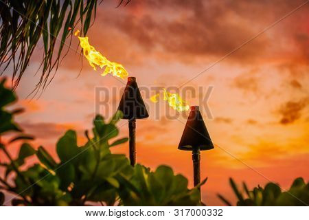 Hawaii luau party Maui fire tiki torches with open flames burning at sunset sky clouds at night. Hawaiian cultural travel vacation background.