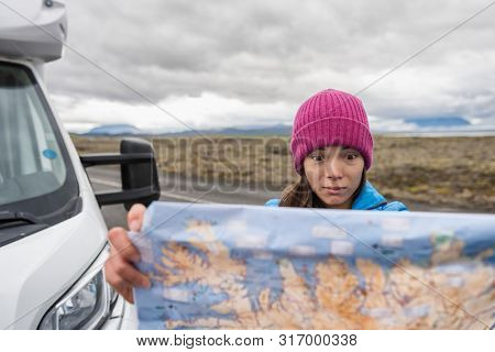 Lost tourist on Iceland road trip looking for directions on travel map driving motorhome campervan on Europe adventure vacation. Asian funny face woman holding map.