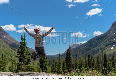 Woman Leaps In Front Of Montana Wilderness In Early Summer