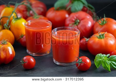 Fresh tomato juice in a transparent glass and ripe tomatoes on the background. Tomato Fresh. Tomato juice and basil. Homemade tomato juice.