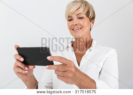 Image of happy adult woman with short blond hair wearing earpods and holding cellphone isolated over white background in studio