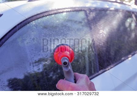 Car Warhing. Worker Cleaning White Car On Open Air.cleaning Car Using High Pressure Water. Man Washi