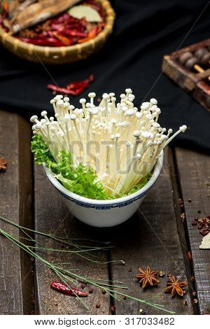 Fresh Needle Mushroom In A White Ceramic Dish