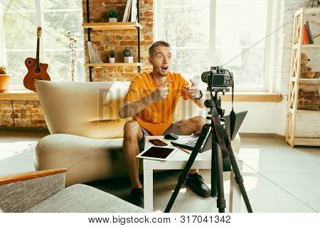 Young Caucasian Male Blogger With Professional Camera Recording Video Review Of Gadgets At Home. Blo