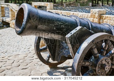 Antique Cannon Stands On The Pier With Paved Paving Stones Against The Background Of The Forest. Old