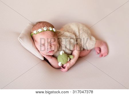 Cute new born child sleeping on pillow with green little toy