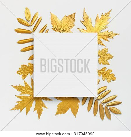Flat Lay Creative Autumn Composition. Paper Blank And Golden Leaves On White Gray Background Top Vie