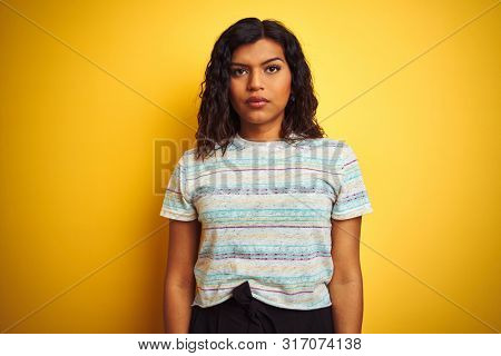 Beautiful transsexual transgender woman wearing t-shirt over isolated yellow background with serious expression on face. Simple and natural looking at the camera.