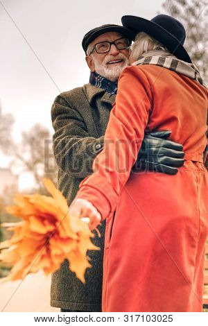 Low Angle Of A Happy Elderly Couple Hugging In Park