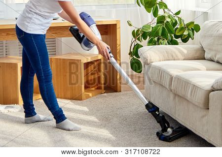Portrait Of Young Woman In White Shirt And Jeans Cleaning Carpet Under Sofa With Vacuum Cleaner In L