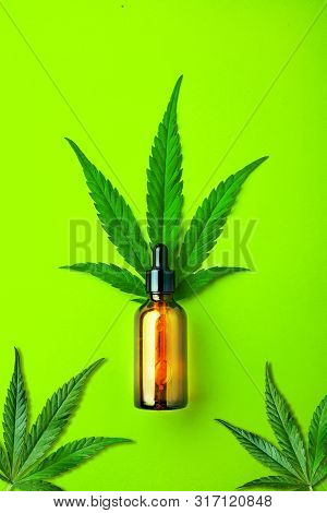 Glass Brown Bottle With Cbd Oil And Cannabis Leaves On Green Background. Minimal Cbd Concept. Flat L
