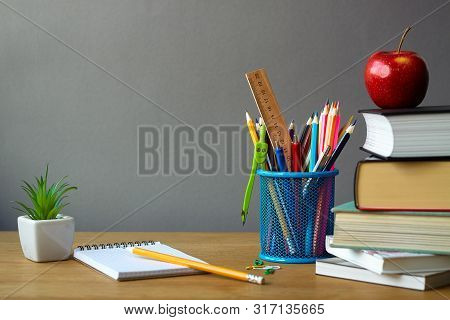Back To School Concept, School Supplies, Stack Of Books, Red Apple, Succulent In A White Pot And An