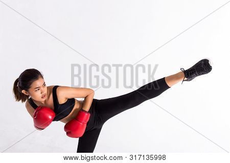 Young Asian Woman In Black Sportswear And Red Leather Boxing Gloves Practicing Kickboxing With Raise
