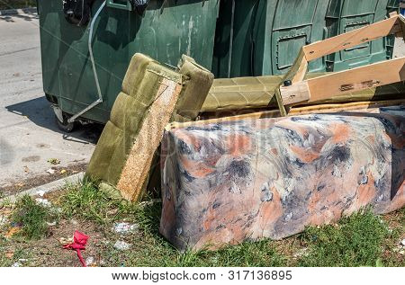 Home furniture thrown in the garbage on the street in the city near plastic dumpster cans littering and polluting the town and environment as junk and trash poster
