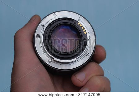 Open Camera Lens In A Hand On A Blue Background