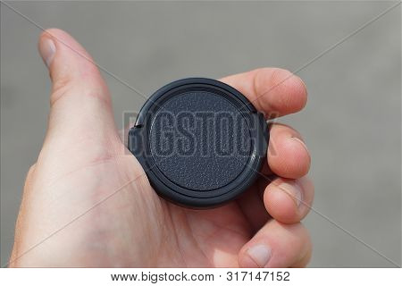 Hand Holds A Black Plastic Lens Cap On A Gray Background