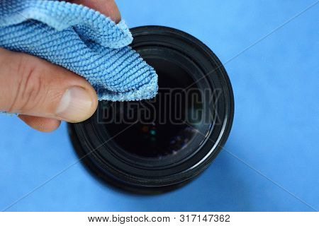 Fingers Hold A Blue  Napkin And Clean The Glass On The Lens Of The Camera