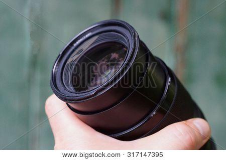 One Black Open Camera Lens In A Hand On A Green Background