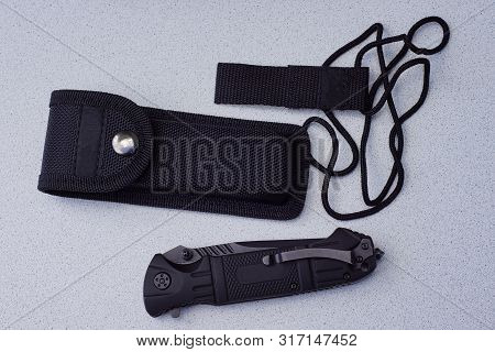 A Set Of Black Folding Knife Cover And Lace Lies On A Gray Table