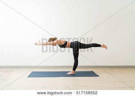 Side View Of Young Female Doing Workout With Virabhadrasana Iii By Wall In Studio