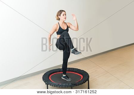 Energetic Young Woman In Sportswear Trampolining Against White Wall During High Intensity Interval T