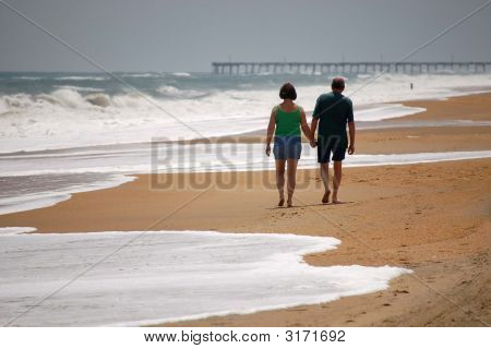 Couple Walking On Beach In The Surf