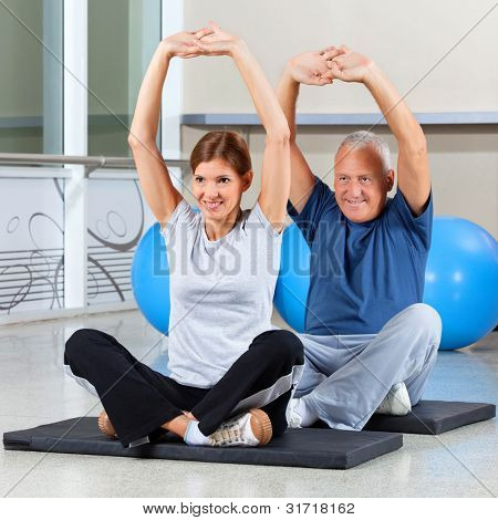 Elderly fitness group stretching their muscles on gym mats in fitness center