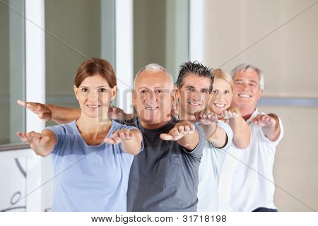 Group of happy senior people doing back exercises in fitness center