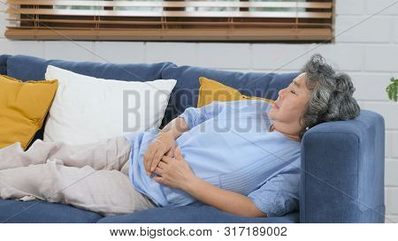 Senior Asian Woman Sleeping On Sofa, Asian Female Elderly Take A Nap At Home Living Room In Day, Old