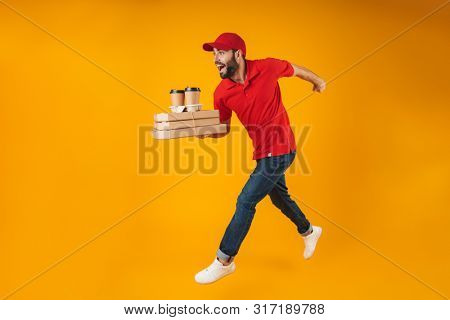 Portrait of young delivery man in red uniform running with pizza boxes and takeaway coffee isolated over yellow background
