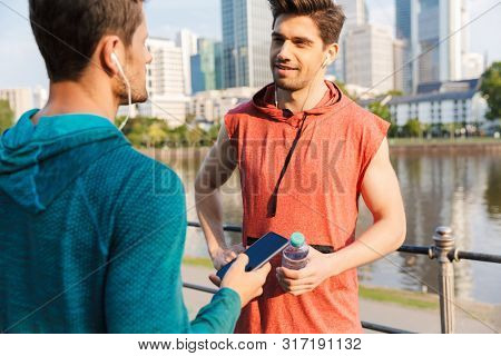 Photo of two strong sporty men wearing sportswear using cellphone and earphones while talking on city riverfront