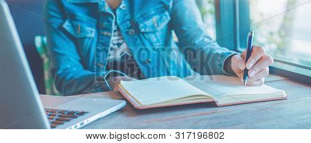 Woman Hand Is Writing On Notebook With A Pen In The Office.web Banner.