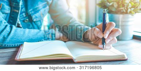 Woman Hand Is Writing On Notebook With A Pen In The Office.