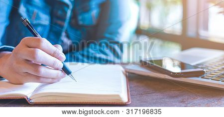 Woman Hand Is Writing On A Notepad With A Pen.on The Table, There Are Laptops And Mobile Phones.