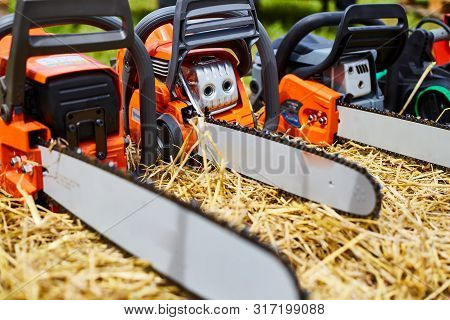Electric Chainsaws Close Up. Building Tool. Orange Chainsaw.