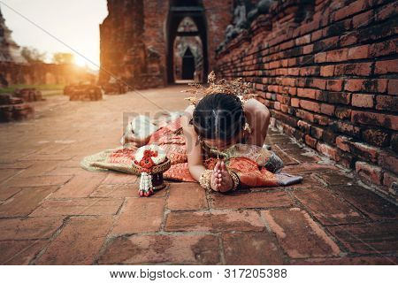 Portrait Of Beautiful Asian Woman Pay Respect In Ancient Temple With Steering Wheel (this Image For