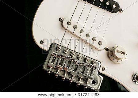 Black And White Electronic Guitar Close Up View. Details Of Rock Guitar. Strings And Volume Control.
