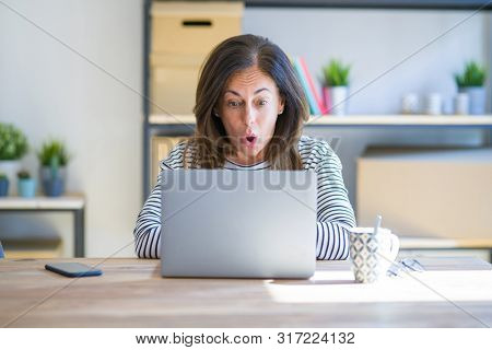 Middle age senior woman sitting at the table at home working using computer laptop afraid and shocked with surprise expression, fear and excited face.