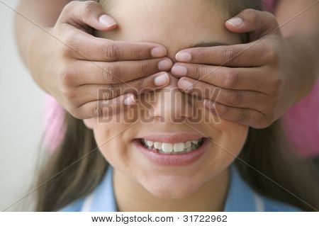 Close up of girl with hands over another girls eyes