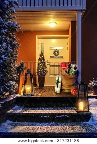 Welcome Christmas - House Entrance Snowy Steps And Door With Decoration. Santas Present Sack With Gi