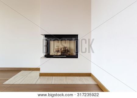 Detail of fireplace with wooden logs and white wall. Close up