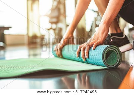 Close Up Of Sporty Woman Folding Yoga Mattress In Sport Fitness Gym Training Center Background. Exer