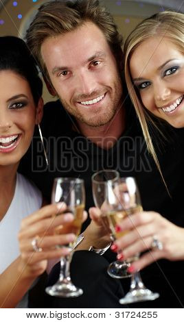 Beautiful young people drinking champagne, clinking glasses, smiling happily.
